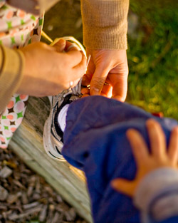 An adult tying the shoes of a child