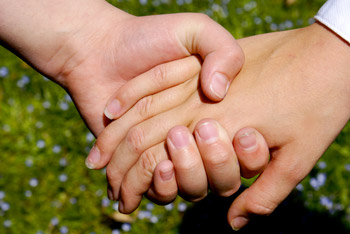 Closeup of a child's hand being held by an adult