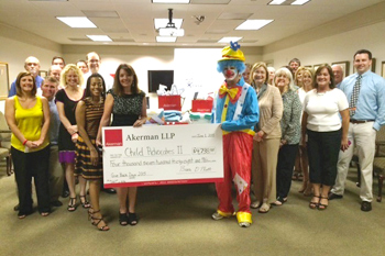 Akerman LLP Tallahassee staff present Circuit Director Deborah Moore with a check and household items