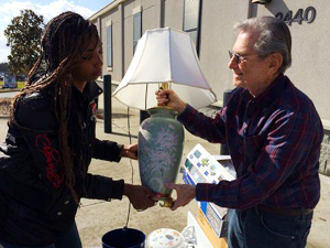 Briahnna Banks taking a lamp from Guardian ad Litem Volunteer Stuart Zirin