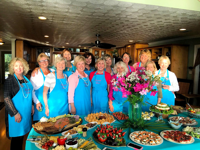 The Dinner Divas pose with food and flowers at The Dinner Divas Present: A Coastal Cocktail Buffet Fundraiser on Saturday, March 12, 2016 in Eastpoint, Florida.