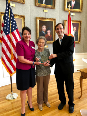 Second Judicial Circuit Guardian ad Litem Program Circuit Director Deborah Moore (left) and Holland & Knight Attorney Kevin Cox present Dorothy 'Dot' Binger with the Glenn J. Winuk Humanitarian Service Award on Tuesday, September 11, 2018 in Tallahassee, Florida.