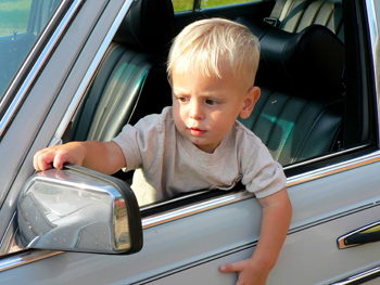 Original Photo Credit: Neil Smith --- adjusting the mirror (a little boy adjusting the driver's mirror of a car through the open window)