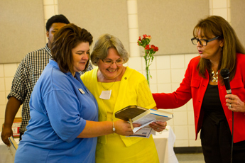 Original Photo Credit: David July/gal2.org --- Volunteer team leader Jan Watford accepting an award and book from Kimberly Nester with Circuit Director Deborah Moore during the awards ceremony at Guardian ad Litem Appreciation Day on June 15, 2013 in Tallahassee, Florida.
