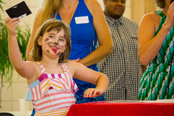 Original Photo Credit: David July/gal2.org --- Young Skylar hands a prize to a raffle winner during the awards ceremony at Guardian ad Litem Appreciation Day on June 15, 2013 in Tallahassee, Florida.