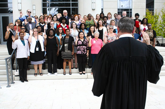 Photo Credit: The Florida Bar News (Fourth Judicial Circuit Judge David Gooding swearing in a new class of seventy-five guardians ad litem in front of the Duval County Courthouse in October 2013)