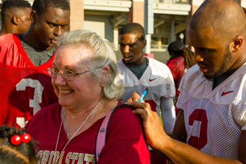 Original Photo Credit: David July/gal2.org --- Guardian ad litem guest and volunteer Jan Watford with Florida State Seminoles football players at the Albert J. Dunlap Athletic Training Facility football practice fields in Tallahassee, Florida on October 8, 2013.