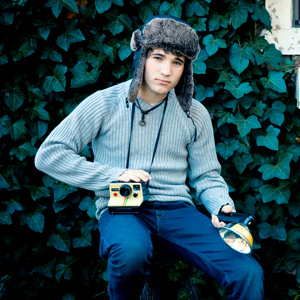 A teenage boy holding a classic Polaroid camera and flash