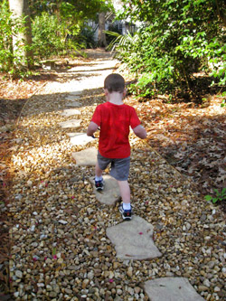 A young boy walking along a path of stepping stones
