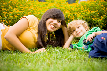 A woman lays in the grass next to a young boy