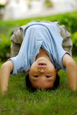 A young boy upside down on all fours