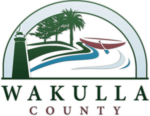 Wakulla County logo with a lighthouse, rowboat and a shoreline with trees