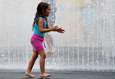 A little girl playing with friends in a fountain on a hot day