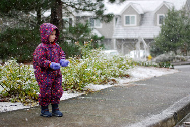 A young girl in a purple snow suit outside in the snow