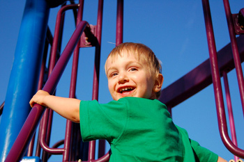 A young boy on a jungle gym under a blue sky in June