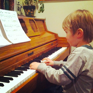 A young boy playing a piano with sheet music