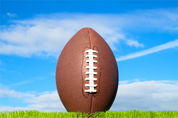 American football in green grass in front of a cloudy blue sky