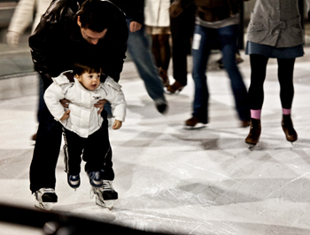A man helping a child to ice skate