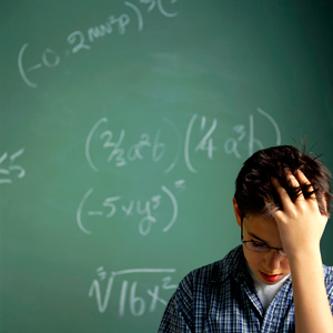 A boy in front of a chalk board with math problems looking down with his hand in his hair