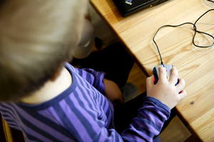 A young boy using a computer mouse on a wooden table