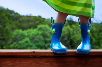 A young girl in a green dress wearing blue rain boots