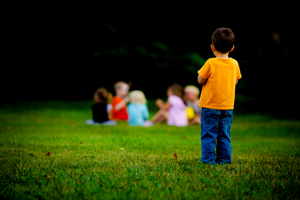Original Photo Credit: charamelody --- 140:365 – Left Out (A little boy stands alone looking at a group of children sitting in a circle)