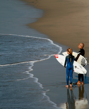 Original Photo Credit: Morgan Johnston --- Waiting (a boy and a girl with surf boards stand at the shoreline)