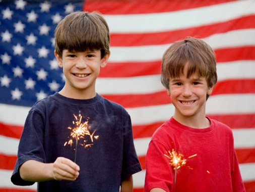 Two young boys with sparklers standing in front of a U.S. flag