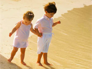 Two young girls holding hands along the water at the beach