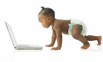 A baby crawling to a notebook computer