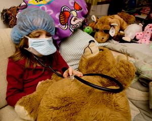 A little girl using stethescope on a teddy bear