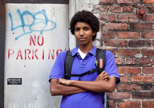 Young man standing in front of a brick wall with graffiti and 'no parking' written on it