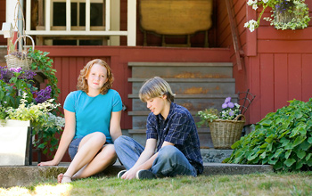 A young woman and teen boy sitting in the grass in front of a home