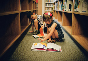 A little girl and boy sitting on a library's floor reading