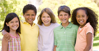 Three girls and two boys smiling in a group