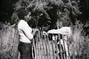 Two young women talking with a wooden fence separating them