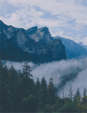 Fog flowing between dense forestland and ragged mountaintops at an unknown location