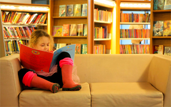 Little girl reading in a library