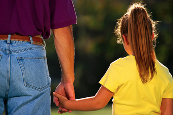 A young girl holding hands with an adult male