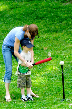 A woman helps a child play tee ball in a park